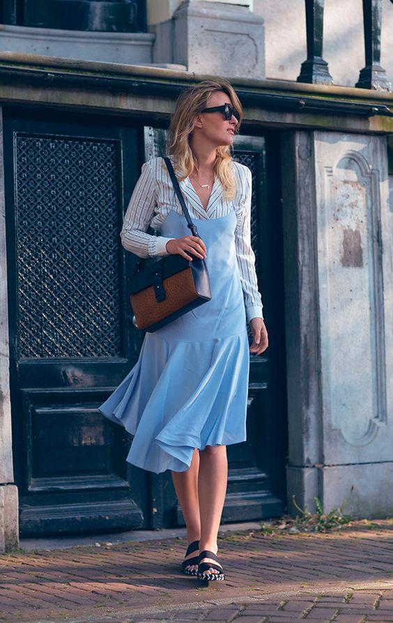Rebecca Laurey usa camisa de listras, vestido de alça azul com sandálias