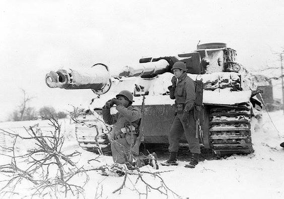 American soldiers with a destroyed Tiger I tank, which is a rare appearance during the Ardennes offensive.