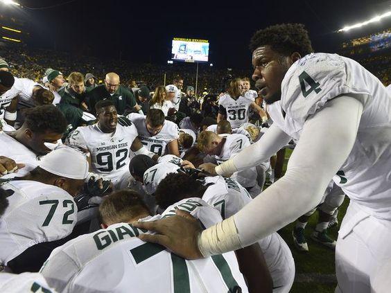 Michigan State players, including Malik McDowell pray