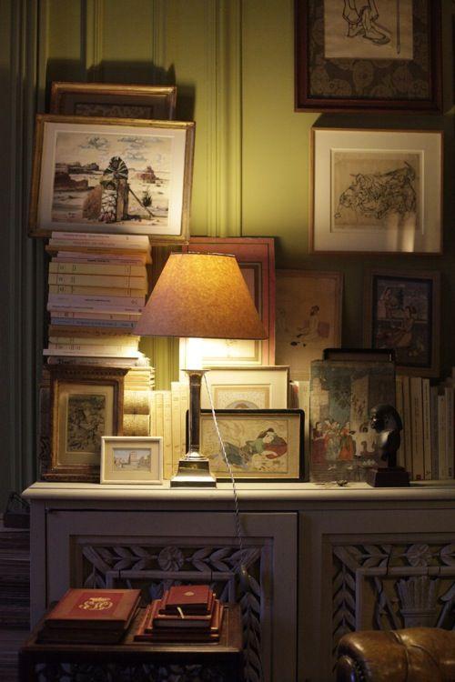 Chez Pierre Le-Tan, j'adore les murs couleur tilleul, les tableaux, les livres empilés et la lumière chaleureuse de l'abat-jour