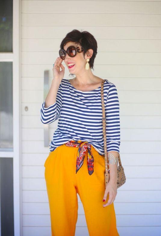 blusa de manga 3/4 listrada azul marinho, lenço na cintura vermelho, azul e amarelo, pantalona mostarda de linho, sandálias espadrilhes douradas, bolsa pequena em tom cru: