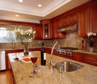 Brilliant red tones in these cabinets make the granite countertops look almost red themselves. It's definitely a fun accent and color and it's one that looks fun, even creeping up the walls as a backsplash.