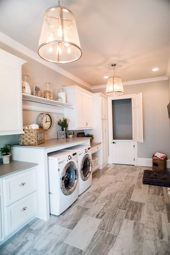 Laundry room. Laundry room flooring is porcelain tiles. Laundry room lighting is from Circa Lighting. Laundry room Countertop is. Caesarstone Pebble Honed Quartz. Laundry Room Paint Color is Sherwin Williams Silverplate. #LaundryRoom Distinctive Remodeling Solutions, Inc.