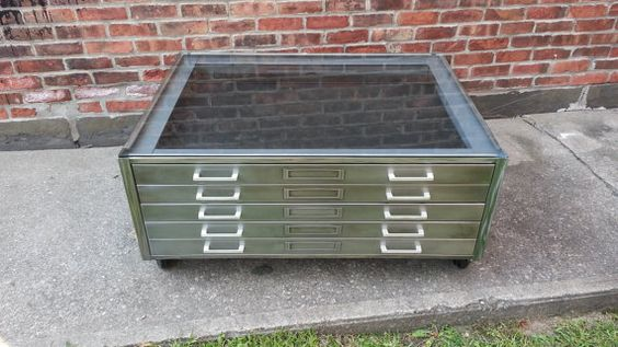 Beautiful vintage flat file cabinet has been turned into a gorgeous, brushed steel, rolling coffee table with glass top. This industrial coffee table is right at home in a large open loft apartment. Originally built for storing maps, blueprints, drawings or large photos. Dimensions: 40w x 28d x 18h  ~ Four inch caster wheels have a rubber coating & make it easy to move without damaging floors  ~ Surfaces (top, drawer fronts, back & sides) have been stripped and wire brush textured BY HAND…