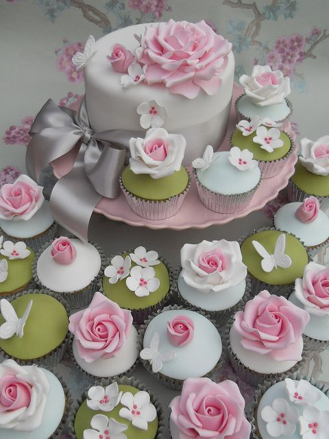 Beautiful floral themed cupcake and wedding cake display in a palette of white, pink, and green using butterflies and a variety of flowers
