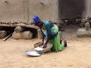マリのドゴン村で石器使用の料理準備中の母親