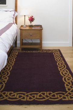 """Celtic Rug - """"Eternity"""" Wool Rug - Plum. This Celtic Rug is handmade from wool and has a distinctive gold knot border, which is truly a design icon. In any home setting, its wool pile is deeply luxurious and retains a soft feel. This wool area rug is handmade and carries a unique piece number to identify its origin. This Irish Rug comes in a variety of sizes and colors to fit any room in your house! Sizes 12' x 2' 8"""", 2' x 8', 4' x 6', 5' x 8', 6' x 9', 9' x 12'."""