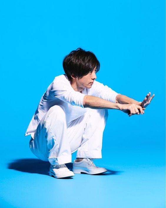 ブルーをバックに白いシャツを着てしゃがんでいる高橋一生の画像