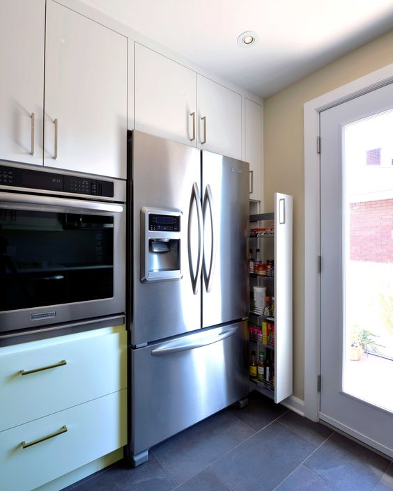 Pull-out storage pantry with wall oven and tall cabinet in white ...