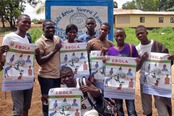 Members of the Plan-supported Kids Arise youth group with ebola posters to post in their community to help curb the spread of the disease.