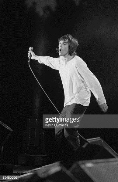 Singer Ian Brown performing with British rock group The Stone Roses at an outdoor concert at Spike Island, Widnes, Cheshire, 27th May 1990.