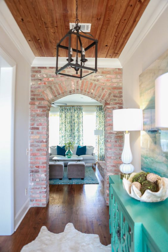 Hallway. Brick wall with arched door. Warm wood ceiling with white trim. Turquoise painted hall table. Lantern pendant.