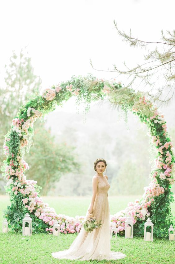 A wedding backdrop that frames rather than hides a venue's beautiful surrounds! This giant pink floral wreath is what dreams are made of! // Gerry and Devina's Engagement With a Giant Floral Wreath at Pine Forest, Bandung {Facebook and Instagram: The Wedding Scoop}: