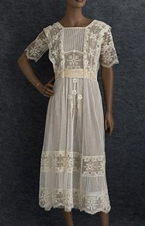 Filet lace and tulle tea dress, c.1918. The transitional style features the square neckline popular at the end of WWI.The dress is finely embellished with rows of narrow tucks and wide panels of handmade filet lace. The occasional Irish crochet flowers add to the textural appeal of the monochromatic design.