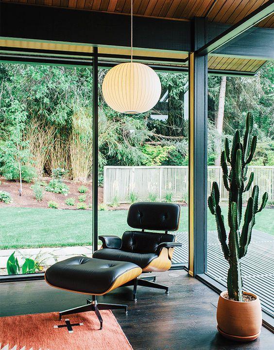 Na forma verdadeira meados do século, uma bolha Lamp George Nelson está emparelhado com um Salão Eames por Charles e Ray Eames em um canto da sala de estar.  As paredes de vidro e canto mitered são características originais de 1956 o projeto do arquiteto Saul Zaik.