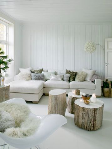 White on whites living room.  Love the logs for the cocktail table, that could double as seating if needed. Anything with white sheepskin is gorgeous in my book too...