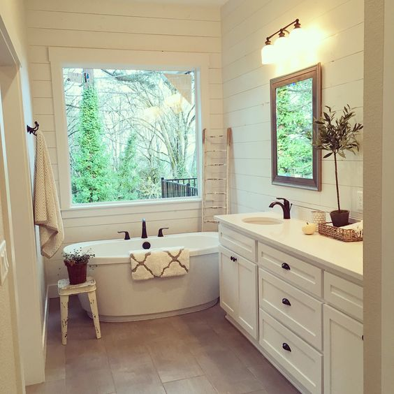 This master bath. The shiplap, freestanding tub, and modern farmhouse touches make it a true retreat. Interior design by Janna Allbritton of Yellow Prairie Interior Design.: