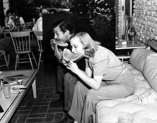 Clark Gable and Carole Lombard eating watermelon.