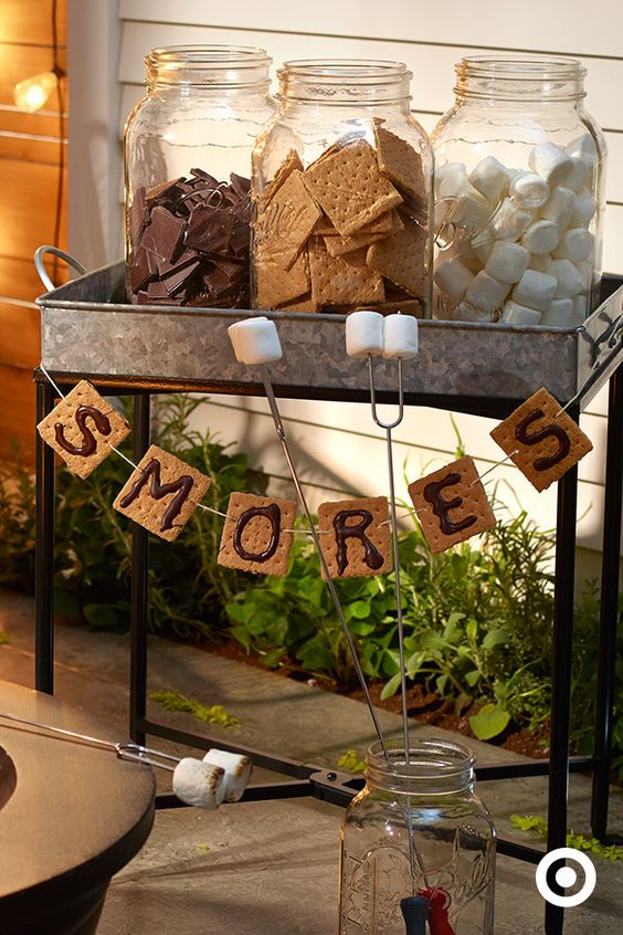 Set up a build-your-own s'mores bar sure to wow with adorable—and edible—garland. Here's how: 1. Gently thread graham crackers together with twine and a large needle, leaving twine on either end for hanging. 2. Melt chocolate in a plastic bag. 3. Once melted, cut a corner of the bag and use it to pipe the letters onto your grahams. 4. Place the garland in the refrigerator for a few minutes to cool. 5. Hang it on the s'mores bar, and bring on the sugar rush!