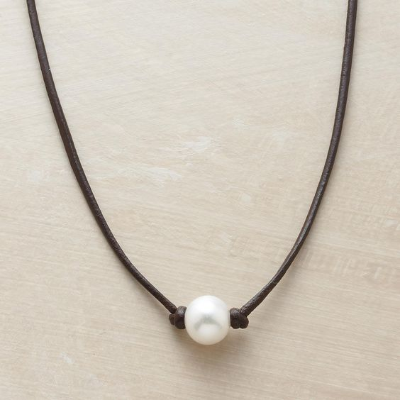"ENCHANTED PEARL NECKLACE�--�Simply knotted on a leather strand, a cultured pearl's inborn luster becomes all the more enchanting in a handmade pearl necklace by Rebecca Lankford. Sterling hook and leather loop closure. Handmade in USA. 16""L."