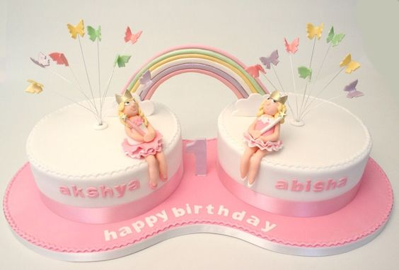 This was a birthday cake I designed for twin girls. The mum asked that there be a rainbow in the design and 2 cakes so I decided to make my own board and have 2 cakes with sugar modelled fairy princesses and a rainbow joining the 2 cakes in pastel colours
