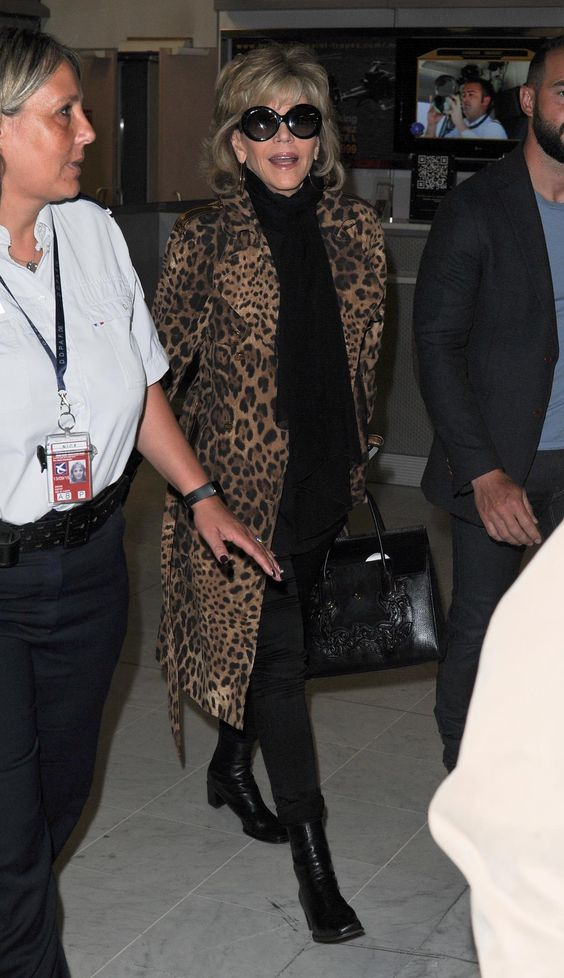 Jane Fonda rocked a trendy leopard print coat as she was escorted through Nice Airport by French police as she arrived for the Cannes film festival.