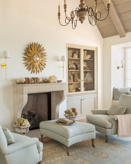 A gorgeous French Country sitting area in a beach house bedroom with French limestone fireplace, Aidan Gray chandelier, sunburst and built-ins. #giannetti #aidangray #FrenchCountry