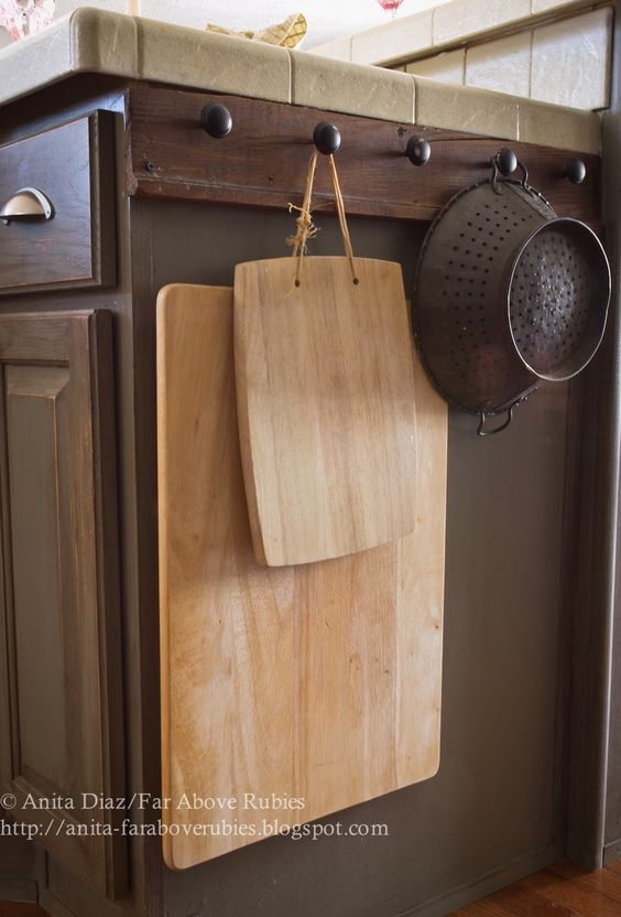 Rather than use space in her cabinets, blogger Anita Diaz added a piece of reclaimed wood to her kitchen island in order to hang cutting boards, pots, and pans.  Get the tutorial at Far Above Rubies.    - CountryLiving.com