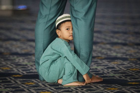 A young Malaysian Muslim child peeks while his father prays during the Islamic holiday of Eid al-Adha at a mosque in Shah Alam outside Kuala Lumpur, Malaysia. Muslims in the country start celebrating Eid al-Adha, or the Feast of the Sacrifice, which honors the prophet Abraham for his willingness to sacrifice his son Ishmael on the order of God who was testing his faith.