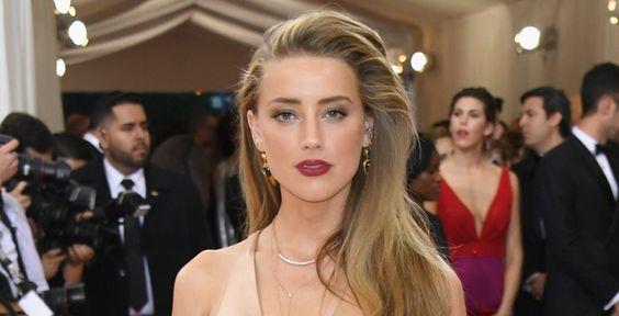Em oposição ao seu look de tom neutro, Amber Heard escolheu um batom vermelho queimado, dando vida ao visual: