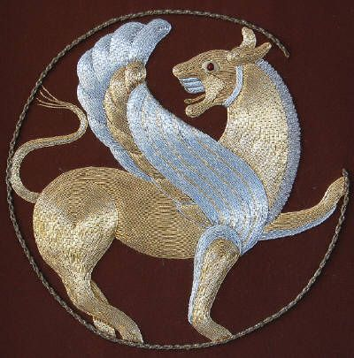 """Jane Zimmerman: Griffen, adapted from a 6th-9th century BC Persian stone """"lion roundel"""". Executed in 1976 on a silk ground, primarily in gold and silver Japan metal in addition to silver kid, gilt and silver twisted cord (tarnished) and silver twist over multiple layers of felt to produce the sculptured appearance."""