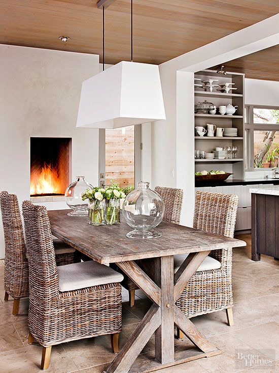 Strike a balance between cozy and sleek with a contemporary design with farmhouse references. This serenely hued dining room does that and more. A trestle table crafted from reclaimed wood and new wicker chairs make a collected statement below a thoroughly modern light fixture. A recessed firebox, dark wood ceilings, and stony floor tiles enhance warmth without disrupting the calm.: