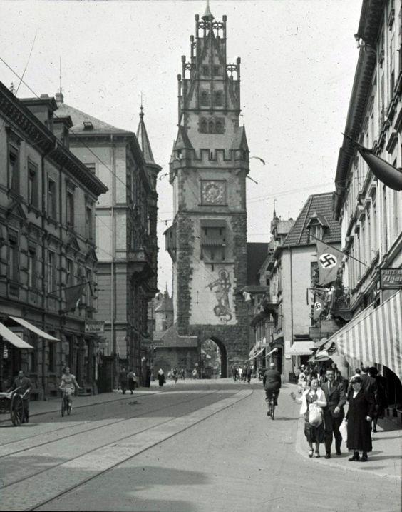 Schwabentor Freiburg 1937    Zeitgenössische Darstellung des Schwabentor Freiburg aus dem Jahre 1937. Bei diesem Bild sind leider auch die zu dieser Zeit selbstverständlichen Fahnen mit den nationalsozialistischen Symbolen zu sehen. Wenn auch ein dunkles, so war es doch auch ein Kapitel das zu un