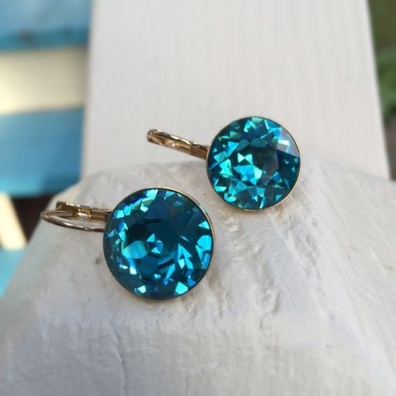 Bella type earrings made with Swarovski crystals Brand-new earrings made with genuine Swarovski crystals in a beautiful indicolite shade bella style gold tone setting.  My husband and I make jewelry using genuine Swarovski crystals. All items are new and much prettier in person than pictures. Proceeds used to help our 5-yr-old granddaughter Lila May in her fight against cancer, but she lost her battle. Now she is dancing with the angels.  A percentage of profit will go to help pay for her…