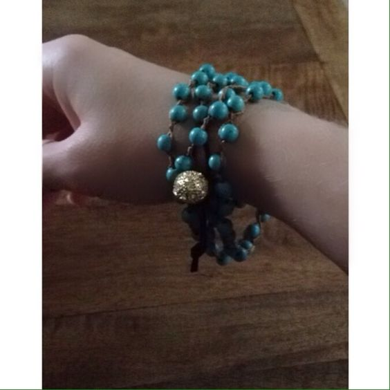 "Torquise wrap style bracelet Designed to wrap around the wrist, the bracelet is crafted by hand with beads of reconstituted turquoise fastened by a large gold and crystal bead. 35"" Jewelry Bracelets"