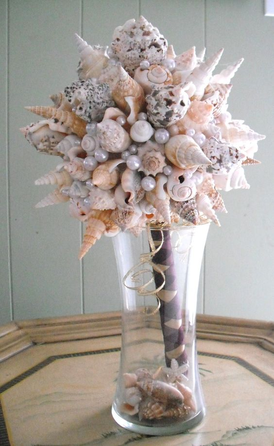 "My seashell Wedding Bouquet.  (I also made my bridesmaids bouquets)  used a wooden rod cement glued it into the styro foam ball.    wrapped rod with ribbon.    cement glued the shells into the styro foam ball.  glued ""pearls"" to fill the gaps.   The shells were ordered from www.deltonaseashells.com    It's now used as decor in my home! :o)"