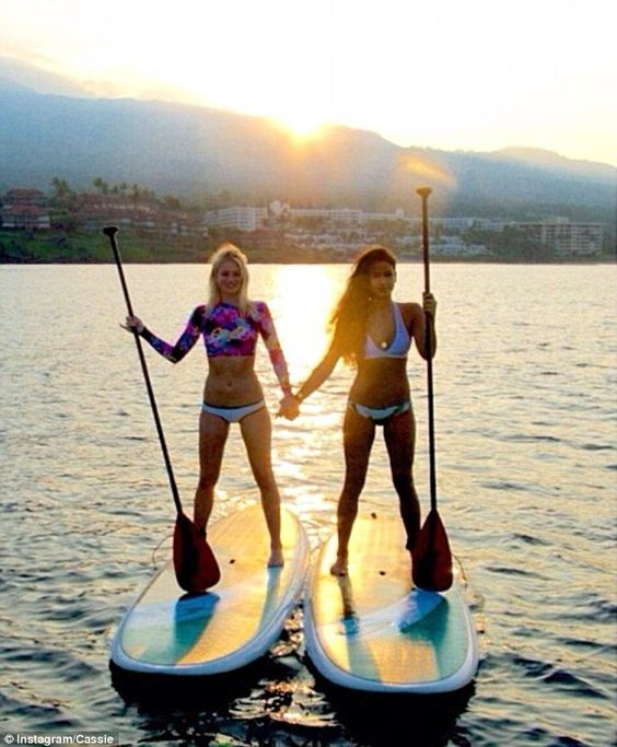 Double act: Cassie and her friend brave the waters at sunset...but not before posing for a...