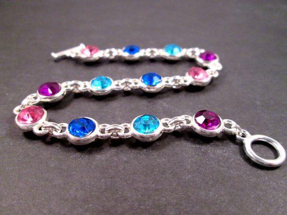 Diamantes tallados son de acrílico y los valores de plata brillantes son aleación de metal (níquel-libre y sin plomo, por supuesto) y por eso este pulsera colorida que se parece a 1 millón, es sólo $14. Azul aqua brillante y rosa, violetas púrpura y zafiro piedras azules en los entornos de 8mm, con eslabones plata doble y un cierre de palanca.  Pulsera se ajusta hacia arriba a una muñeca de siete pulgadas, pero puede ser alterada, bajo petición.  Ver más de mis diseños de joyería…