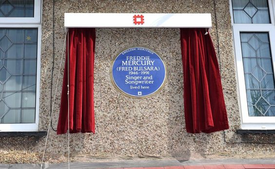 """Four days ahead of what would have been Freddie Mercury's 70th birthday, the Queen singer's first home in England was given an honorary blue plaque to indicate he once lived there. The Thursday ceremony in London featured Queen guitarist Brian May and Mercury's sister, Kashmira Cooke, unveiling the plaque.  """"Mum and I are so proud and pleased that English Heritage is honouring our Freddie with a Blue Plaque, and that he will be amongst other famous names forever,"""" Cooke said. """"Secretly he…"""