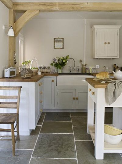 Sweetly serene English style kitchen with rustic beams, farm sink, Shaker cabinety, and stone flooring. #whitekitchen #kitchendesign #farmhousestyle #English #Europeankitchen #shaker #farmsink