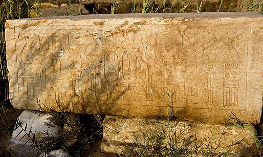 A block with fine, clear reliefs rests on stones at Buto