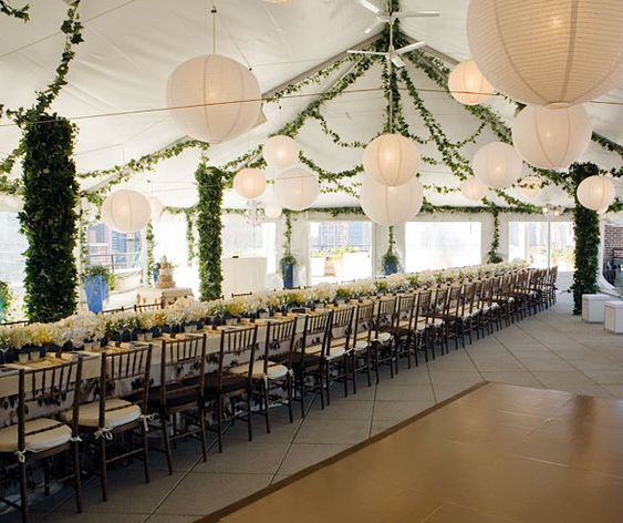 A White Tent Decorated With Ivy And Paper Lanterns Covers