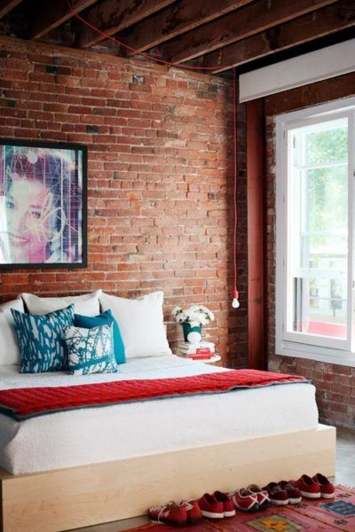 Exposed brick walls in this industrial cozy bedroom with red details