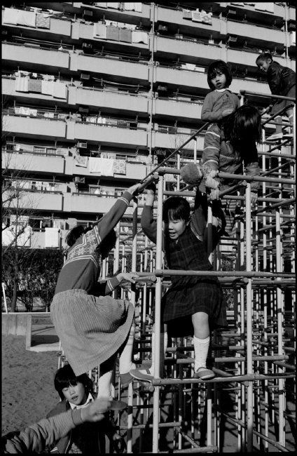 Japan. Tokyo. Children playing on monkey bars at an apartment complex. 1983