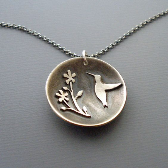 Ive hand cut tiny hummingbird and flower shapes from a sheet of sterling silver using my jewelers hand saw.I then soldered them to a silver circle giving the pendant a concave form. Ive oxidized the piece and Ive given it a soft, brushed finish. The pendant measures 15/16 in diameter. It hangs from a 20 oxidized sterling silver chain. See other items in my shop: http://www.etsy.com/shop/lisahopkins