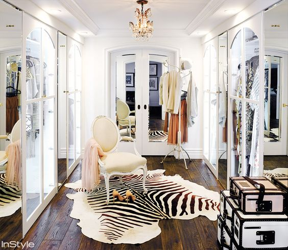 Walk-in closet with Victorian chair and striped rug.