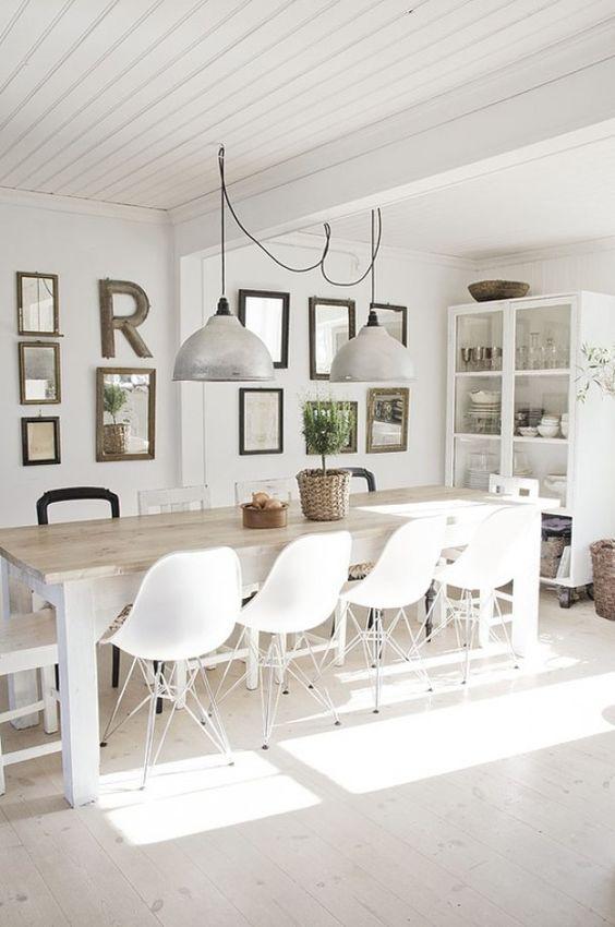 Grote eettafel met moderne witte stoelen en stoere lampen erboven