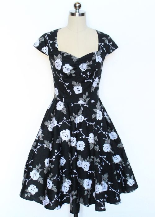 """This beautiful stretch cotton dress features a white & grey rose fabric detail on a black background. It is fitted and lined at the bodice with a sweetheart neckline and gathered at centre bust. The bodice is panelled therefore the pattern will not match up at seams. It features flattering cap sleeves with a waist seam and full circle skirt. It has a hidden zipper in the center back finished with hook & eye fastening at top. It can be worn with a Hell Bunny Short/20"""" length petticoat to…"""