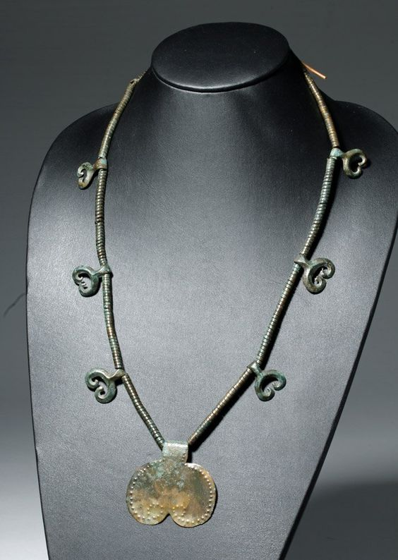 Central Europe, Danube Region, possibly Ottomány (Otomani) culture, Late Bronze Age, ca. 1500 BCE. This is one of our favorite pieces, a beautiful and wearable collection of 3500 year old bronze! The necklace is composed of small, flat beads interspersed with six hanging double lunula pendants; the centerpiece is a large plaque with a punched line of stippling around its front edge. The Danube, Europe's longest river, rises in the Black Forest in modern-day southern Germany, and flows…