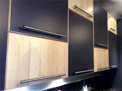 Black cabinetry with timber edging and rail handles.